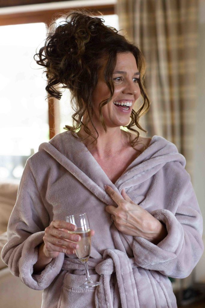 Wedding Photography, Cotswolds, Bridal preparations, Bride smiling wearing a lilac dressing gown holding champagne glass