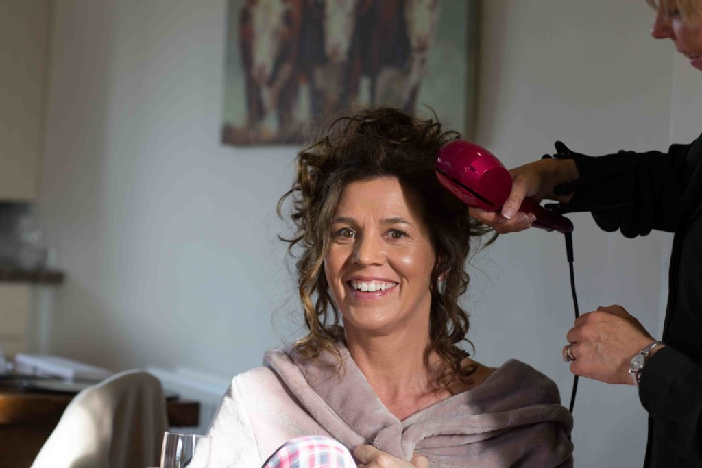 Wedding Photography, Cotswolds, Bridal preparations, Bride sat down smiling wearing a lilac dressing gown and having her hair arranged