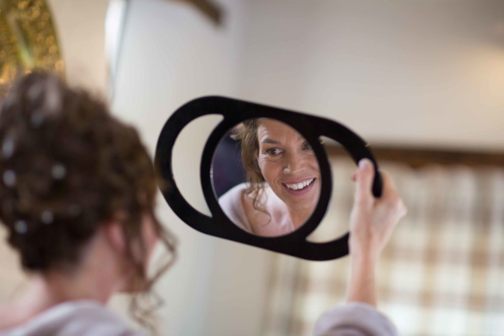 Wedding Photography, Cotswolds, Bridal preparations, Bride smiling and looking at her makeup in a small mirror